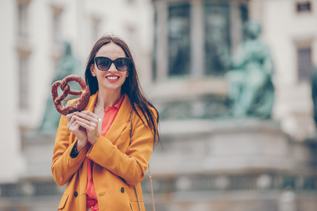 Beautiful young woman holding pretzel and relaxing in park