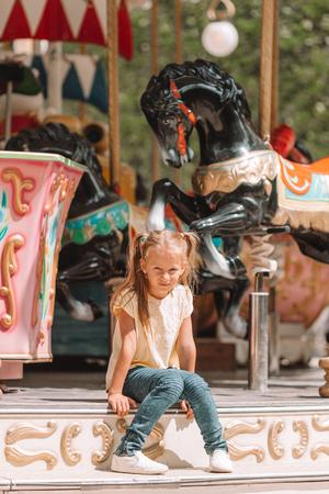 Adorable little girl near the carousel outdoors Stock Photo
