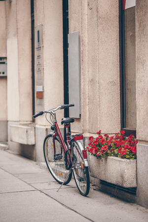Beautiful city landscape with a bike near the old wall with flowers in Vienna