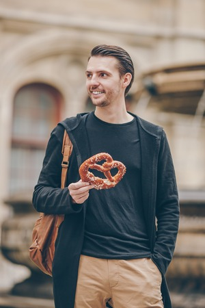 Beautiful young man holding pretzel and relaxing in park