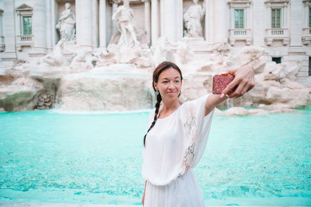Pretty woman looking to the Fountain of Trevi during her trip in Rome, Italy. Girl enjoy her european vacation 版權商用圖片