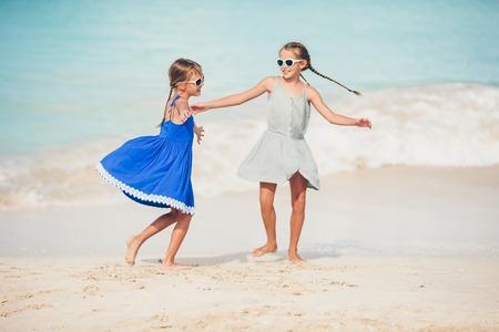Gelukkige kinderen rennen en springen op het strand Stockfoto