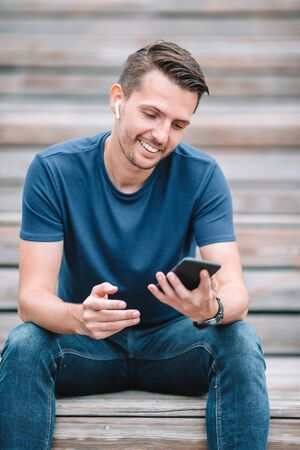 Portrait of beautiful man is reading text message on mobile phone in the park and searching information on smartphone Stock Photo