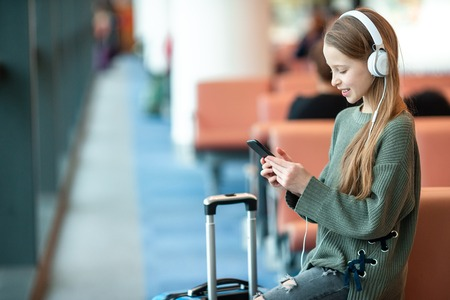 Adorable little girl at airport in big international airport near window Foto de archivo