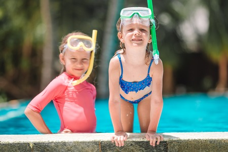 Adorable little girls playing in outdoor swimming pool Stockfoto