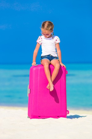 Little adorable girl with big luggage near water villa