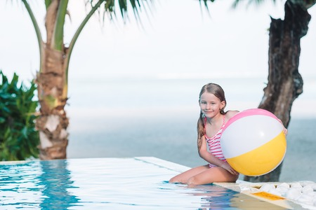 Smiling adorable girl playing with inflatable toy ball in outdoor swimming pool 写真素材