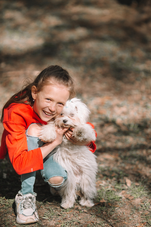 Little girl with a white puppy. A puppy in the hands of a girl