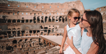 Young mother and little girl hugging in Coliseum, Rome, Italy.