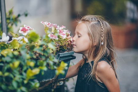 Little adorable girl sitting near colorful flowers in the garden