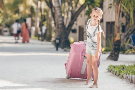Little adorable girl with big luggage during summer vacation