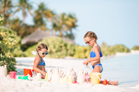Happy little girls playing with beach toys during tropical vacation