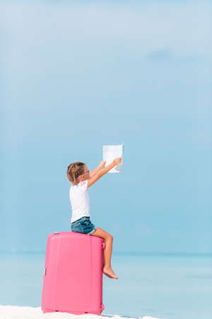 Little adorable girl on the big luggage on the beach with map Stock Photo