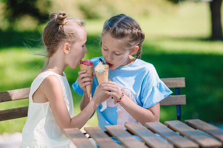 Little girls eating ice-cream at summer in outdoor cafe. Cute kids enjoying real italian gelato Imagens