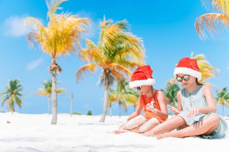 Adorable kids in Santa hats celebrating Christmas on the beach