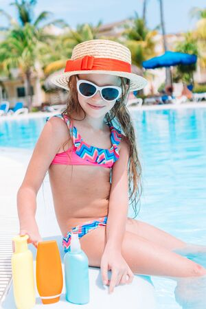 Little girl with bottle of sun cream in swimming pool 版權商用圖片
