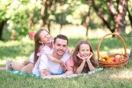 Padre feliz e hijas pequeñas se relajan junto al lago