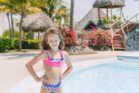 Little girl with bottle of sun cream in swimming pool 스톡 콘텐츠