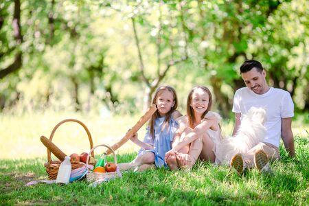 Glücklicher Vater und kleine Töchter entspannen am See