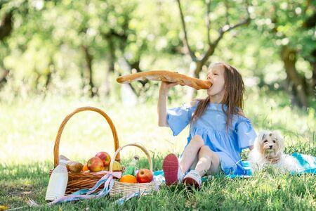 Kleines Kind mit großem Brot beim Picknick im Park