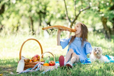 Little kid with big bread on picnic in the park