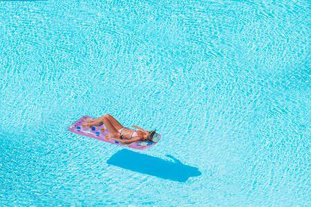 Young woman in bikini air mattress in the big swimming pool