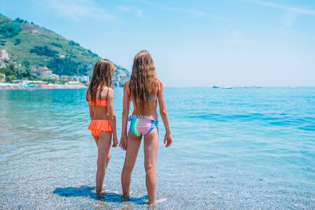Beautiful little girls on the beach in shallow water runs and has fun
