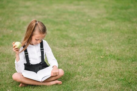 Happy little schoolgirl outdoors rwads the book and eats the apple Stockfoto