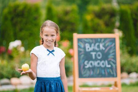Happy schoolgirl with yellow apple background the chalkboard. Back to school