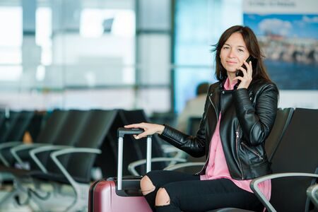 Caucasian woman looking at camera while speaks by phone in the waiting room 스톡 콘텐츠