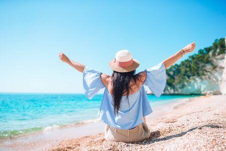 Frau liegt am Strand und genießt die Sommerferien mit Blick auf das Meer Standard-Bild