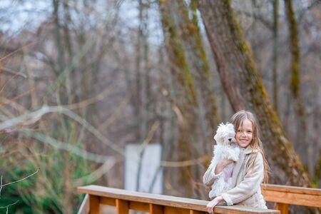 Kleines Mädchen mit einem weißen Welpen. Ein Welpe in den Händen eines Mädchens