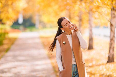 Concetto di caduta - bella donna che beve caffè nel parco autunnale sotto il fogliame autunnale