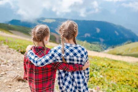 Beautiful happy little girls in mountains in the background of fog Reklamní fotografie