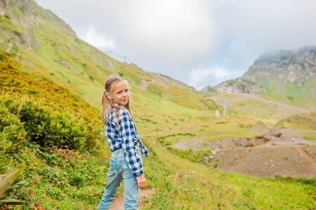 Beautiful happy little girl in mountains in the background of fog Reklamní fotografie
