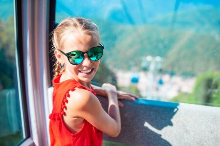 Adorable little girl in the cabin on the cable car in mountains 写真素材