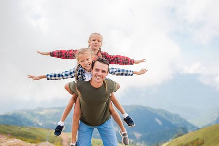 Beautiful kids and happy man in mountains in the background of fog Stock Photo - 136713275