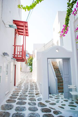 The narrow streets of the island with blue balconies, stairs and flowers in Greece. 写真素材