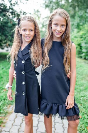 Two cute smilling little girls posing in front of their school. Banque d'images