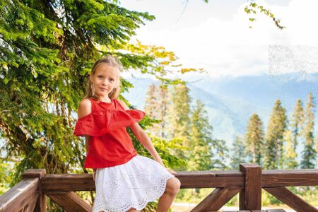 Beautiful happy little girl in mountains in the background of fog 写真素材