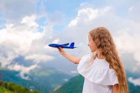 Happy little girl with toy airplane in hands in mountains Stockfoto - 130125650