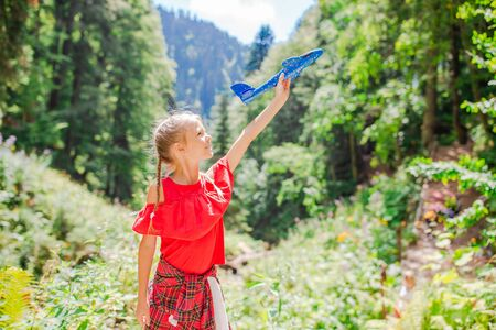 Happy little girl with toy airplane in hands in mountains Stockfoto - 130125646