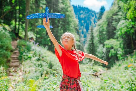 Happy little girl with toy airplane in hands in mountains Stockfoto - 130125742
