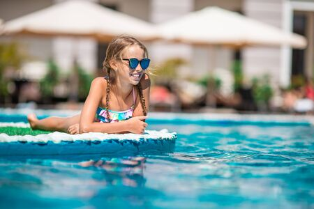 Adorable little girl swimming at outdoor swimming pool Foto de archivo