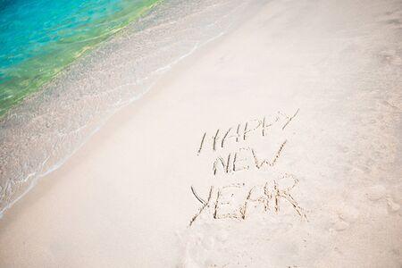 Felice Anno Nuovo scritto nella sabbia bianca