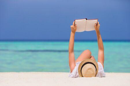 Ritratto di una giovane donna che si rilassa sulla spiaggia, leggendo un libro