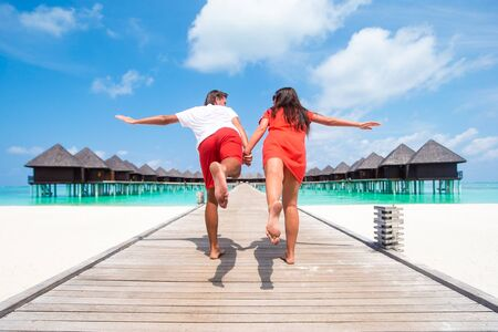 Young couple on beach jetty at tropical island in honeymoon 写真素材