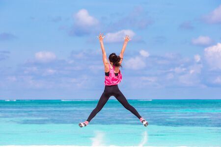 Fit young woman doing exercises on tropical white beach in her sportswear Foto de archivo - 130125823