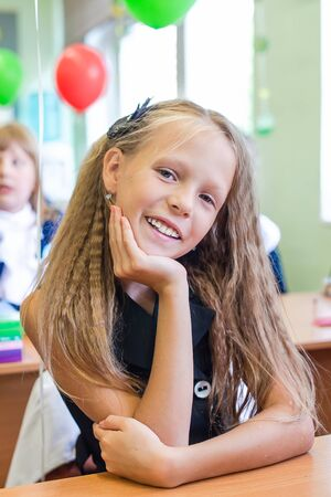 Adorable little schoolgirl in her classroom at the table
