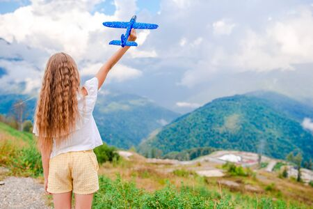 Adorable girl plays on summer vacation in mountains with toy plane